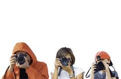 Uomo, donna e ragazzo della mano tenenti la macchina fotografica che prende le immagini su un fondo bianco fotografia stock