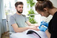 Uomo durante il manicure immagini stock libere da diritti