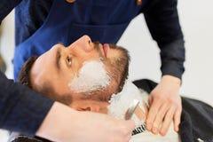 Uomo e barbiere con il rasoio diritto che rade barba fotografia stock