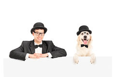 Uomo e cane con i cappelli che propongono dietro il comitato Immagini Stock Libere da Diritti