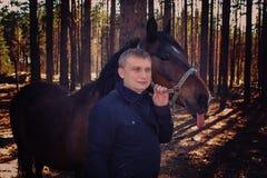 Uomo e cavallo biondi Di autunno scena di luce solare all'aperto Fotografia Stock
