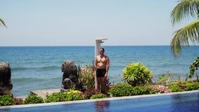 Uomo e doccia sulla spiaggia video d archivio