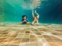 Uomo e donna al fondo dello stagno, si tuffano sotto l'acqua immagini stock libere da diritti
