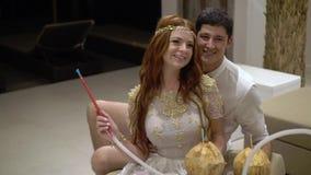 Uomo e donna al partito narghilé divertentesi e di fumo Celebrazione le nozze, un compleanno o dell'anniversario Evento alla a stock footage