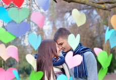 Uomo e donna amorosi nel parco con la decorazione del bacio dei cuori Immagini Stock
