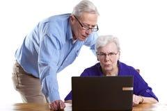 Uomo e donna anziani dietro il computer portatile fotografia stock