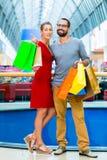 Uomo e donna in centro commerciale con le borse Fotografia Stock