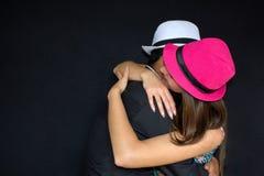 Uomo e donna che abbracciano in cappelli su un fondo nero Forte abbraccio fotografia stock libera da diritti