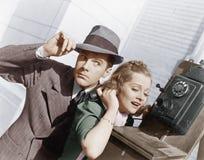 Uomo e donna che ascoltano su un telefono esterno (tutte le persone rappresentate non sono vivente più lungo e nessuna proprietà  Immagine Stock Libera da Diritti