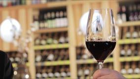 Uomo e donna che bevono vino rosso Mani del primo piano con i vetri Chiuda su delle mani di giovani vetri amorosi di tintinnio de stock footage