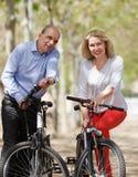Uomo e donna che camminano con le biciclette Immagini Stock Libere da Diritti