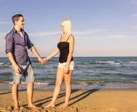 Uomo e donna che camminano e che parlano sulla spiaggia fotografie stock libere da diritti