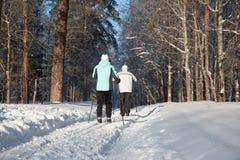 Uomo e donna che camminano sul pattino nella foresta di inverno Fotografie Stock Libere da Diritti
