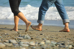 Uomo e donna che camminano sulla spiaggia Fotografia Stock