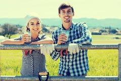 Uomo e donna che chiacchierano e che godono del latte all'aperto Immagine Stock