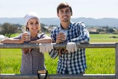 Uomo e donna che chiacchierano e che godono del latte all'aperto Fotografia Stock