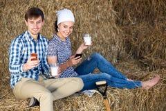 Uomo e donna che chiacchierano e che godono del latte fresco Fotografia Stock Libera da Diritti