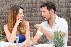 Uomo e donna che discutono a fondo un vetro di champagne Immagini Stock