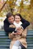Uomo e donna che esaminano smartphone Immagine Stock