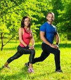 Uomo e donna che fanno allungando gli esercizi Immagini Stock Libere da Diritti