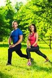 Uomo e donna che fanno allungando gli esercizi Immagini Stock