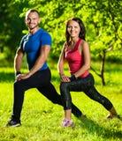 Uomo e donna che fanno allungando gli esercizi Fotografia Stock