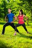 Uomo e donna che fanno allungando gli esercizi Fotografia Stock Libera da Diritti