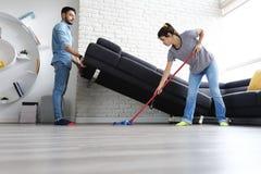 Uomo e donna che fanno i lavoretti che puliscono pavimento fotografia stock