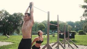 Uomo e donna che fanno i vari esercizi di peso corporeo alla barra orizzontale stock footage