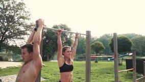Uomo e donna che fanno i vari esercizi di peso corporeo alla barra orizzontale archivi video