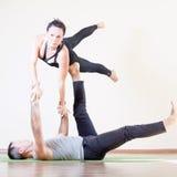 Uomo e donna che fanno yoga di acro o le paia di yoga dell'interno Fotografia Stock