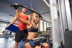 Uomo e donna che flettono i muscoli sulla macchina della palestra Fotografia Stock