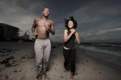 Uomo e donna che funzionano sulla spiaggia Immagine Stock
