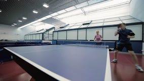 Uomo e donna che giocano un ping-pong contro l'uomo stock footage