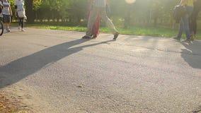 Uomo e donna che godono della data romantica in parco, passeggiata di molta gente, ciclante archivi video