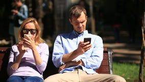 Uomo e donna che guardano nelle direzioni differenti, sedentesi su un banco Ognuno sta esaminando il suo telefono cellulare stock footage