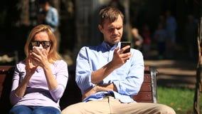 Uomo e donna che guardano nelle direzioni differenti, sedentesi su un banco Ognuno sta esaminando il suo telefono cellulare video d archivio