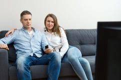 Uomo e donna che guardano TV immagine stock