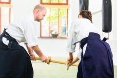 Uomo e donna che hanno lotta della spada di aikidi Immagine Stock