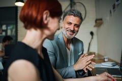 Uomo e donna che hanno riunione d'affari in un caffè, facendo uso del computer portatile fotografia stock libera da diritti