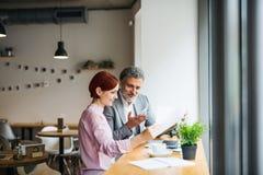 Uomo e donna che hanno riunione d'affari in un caffè, facendo uso del computer portatile immagini stock