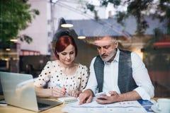 Uomo e donna che hanno riunione d'affari in un caffè, facendo uso dello smartphone fotografie stock