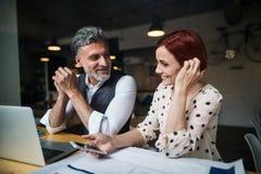Uomo e donna che hanno riunione d'affari in un caffè, facendo uso dello smartphone fotografie stock libere da diritti