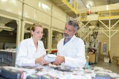 Uomo e donna che ispezionano pacchetto sigillato fotografie stock libere da diritti