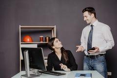 Uomo e donna che lavorano al computer portatile in ufficio Immagine Stock