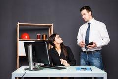 Uomo e donna che lavorano al computer portatile in ufficio Fotografia Stock
