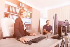 Uomo e donna che lavorano alla linea di aiuto di servizio di assistenza al cliente fotografia stock libera da diritti