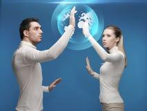 Uomo e donna che lavorano con l'ologramma del globo Fotografia Stock