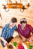Uomo e donna che mangiano alimento nella cabina della montagna Immagini Stock