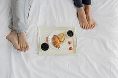 Uomo e donna che mangiano prima colazione in camera da letto fotografie stock libere da diritti